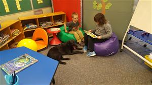 Students sitting next to Bear the Reading Dog.