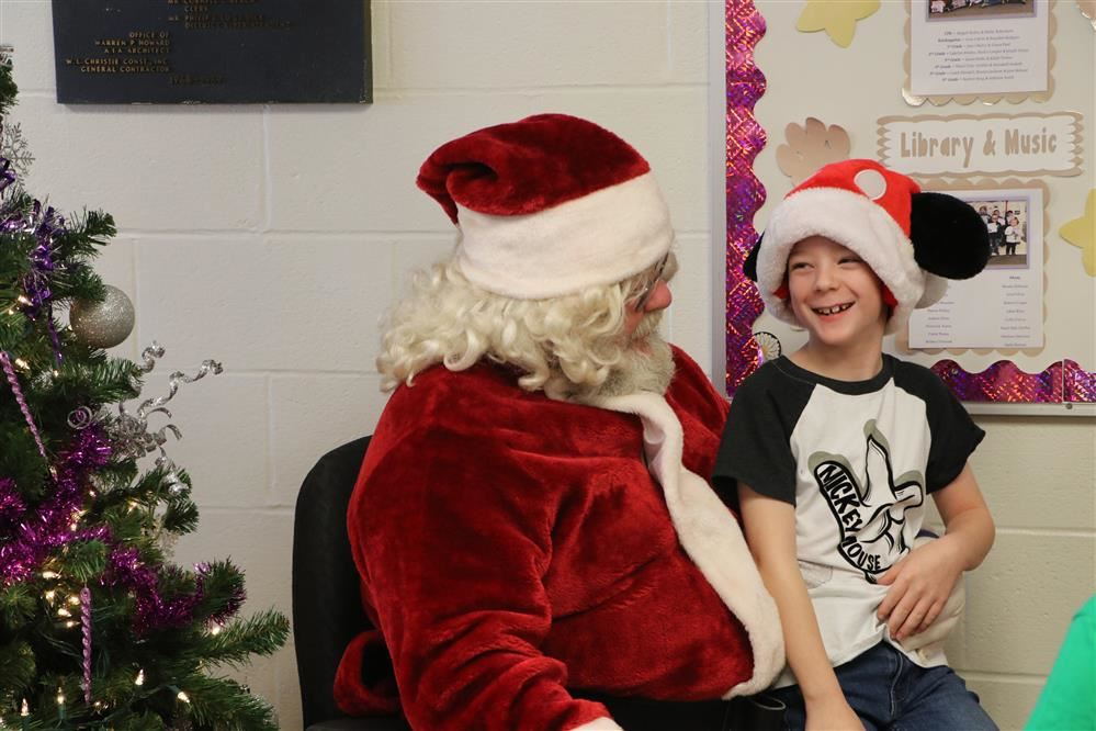 Little boy sitting on Santa's lap and smiling