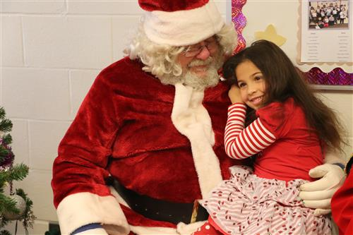 Young girl cuddled up to Santa