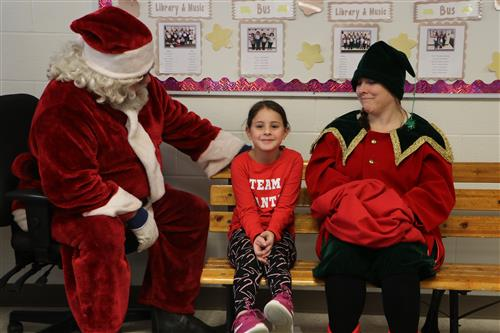 Santa, his elf and a little girl