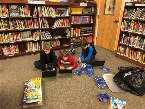 Students coding in the library