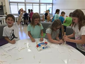 Students building a tower with marshmallows and toothpicks