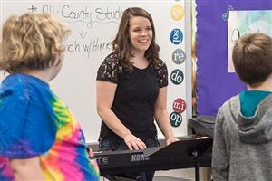 Mary Kay Himes plays the piano and leads children in singing