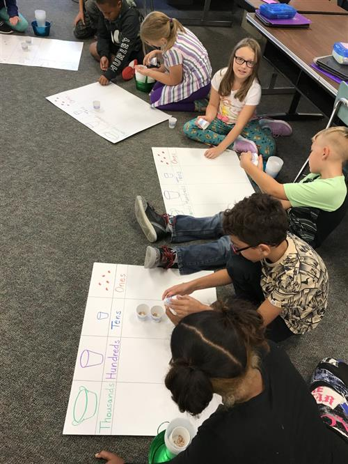 Groups of students working together to bundle beans and count large numbers