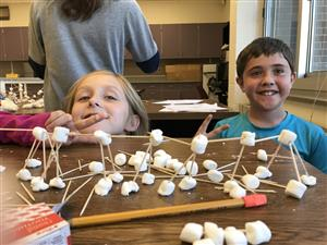 Two students building a bridge with marshmallows